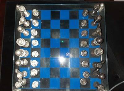 Scacchiera in vetro con scacchi in metallo